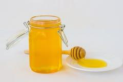Sacuda con el cazo del oney de la miel y del  de Ð en el platillo blanco Fotos de archivo libres de regalías