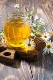 sacuda con la miel de la flor fresca en una tabla de madera oscura, vertical Foto de archivo