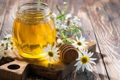 sacuda con la miel en una tabla de madera oscura, primer de la flor fresca Fotos de archivo