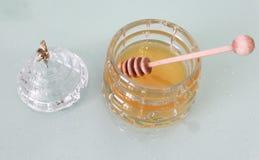 Sacuda con la miel y el palillo de madera, cubierta con la abeja Foto de archivo libre de regalías