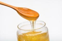 Sacuda con la miel y la cuchara de madera aisladas en el fondo blanco Fotos de archivo