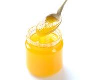 Sacuda con la miel y una cuchara del metal en un fondo blanco Fotografía de archivo