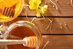 Sacuda la miel con el panal en la opinión de sobremesa de madera Foto de archivo libre de regalías