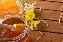 Sacuda la miel con el panal en macro elevada la tabla de madera Imagenes de archivo