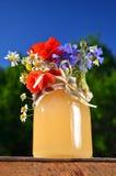 Sacuda por completo de la miel fresca deliciosa y de las flores salvajes en colmenar Foto de archivo