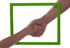 Sacudida de las manos en un marco verde de la foto Imagenes de archivo
