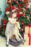 Sacudidas hermosas de la muchacha en una mecedora del caballo Fotografía de archivo