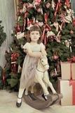 Sacudidas hermosas de la muchacha en una mecedora del caballo Imagen de archivo libre de regalías