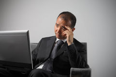 Sad. Asian businessman working on laptop with sad expression royalty free stock photos