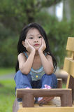 Sad. Little girl sitting on a wooden bench in a park Royalty Free Stock Photos