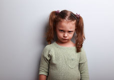 Sad abandoned kid girl looking unhappy. On blue background Royalty Free Stock Images