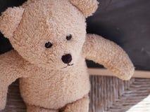 Sad abandoned teddy bear. Sad teddy bear alone on the chair against the black board Stock Photo
