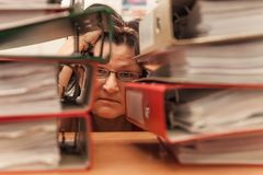 Sad accountant with stack of folders and falling papers royalty free stock photography