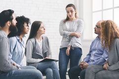 Sad addicted woman sharing her problems at rehab group meeting royalty free stock photos
