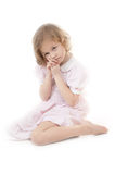 Sad adorable little blonde girl. At the age of five wearing a pink dress sitting pensively on a white background Stock Photo