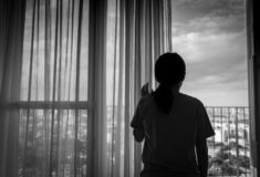 Sad adult Asian woman looking out of window and thinking. Stressed and depressed young woman. Despair women with long hair. And T-shirts standing by the window royalty free stock image