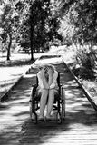 Sad adult woman on wheelchair in the park Stock Photography