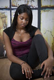Sad african american teen. Sad, worried African American teenager sitting and looking down. Troubled Stock Photos