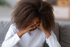 Sad black teenage girl having problems crying a home royalty free stock image
