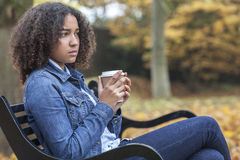 Sad African American Teenager Woman Drinking Coffee. Beautiful mixed race African American girl teenager female young woman drinking takeaway coffee outside Royalty Free Stock Photos