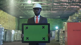 Sad african businessman with chromakey sign. Angry or unhappy african american man engineer in warehouse standing and holding a pad for copy space. Horizontal stock footage