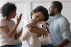Sad african child boy embrace toy upset by parents arguing stock image