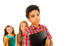 Sad African student standing in the queue. Sad African boy standing with notepad in the queue with other classmates girls Stock Image