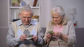 Sad aged couple holding few dollar banknotes, not enough money for food payment stock video