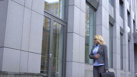 Sad aged woman looking window glass reflection, walking along office building stock video footage