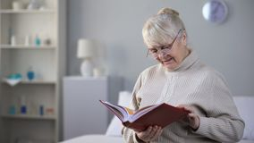 Sad aged woman wearing eyeglasses and watching photo album, missing family. Stock footage stock footage