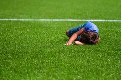 Sad alone kid lying on the football field grass outside stock photo