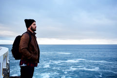 Sad alone man enjoying beautiful ocean landscape in cool autumn  day during his travel Stock Photos