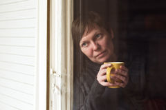 Sad alone Woman Drinking Coffee in Dark Room Royalty Free Stock Images