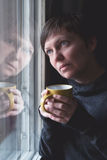 Sad alone Woman Drinking Coffee in Dark Room stock images