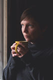 Sad alone Woman Drinking Coffee in Dark Room Royalty Free Stock Image
