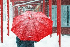 Sad and alone woman walking in snow through urban environment royalty free stock photo