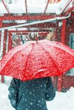 Sad and alone woman walking in snow through urban environment stock photography