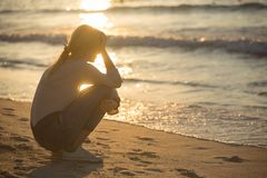 Sad and alone young woman at the beach. Silhouette of a girl against a sunset, girl is dealing with her sadness alone at the beach royalty free stock images
