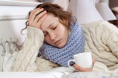 Free Sad Alone Young Woman In White Sweater And Blue Scarf Feeling Headache, Cold Sick And Resting Home In Bed. Holding Her Painful Royalty Free Stock Image - 155813296