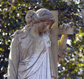 Sad angel. At the cross grave marker stock photography
