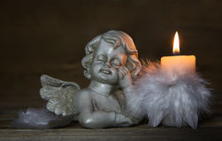 Sad angel with burning candle for bereavement or mourning background stock photography