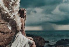 Sad angel looking at the occean. Sad pretty angel looking at the occean Royalty Free Stock Photography
