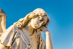 Sad angel. Statue of sad and grieved angel looking down and sustaining her reclined head with hand Royalty Free Stock Image
