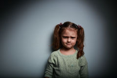 Sad anger kid looking on dark background. With shadows Stock Photos