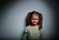 Sad anger kid looking on dark background Stock Photos