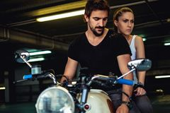 Sad and angry couple sitting on a motorcycle. In a garage royalty free stock image