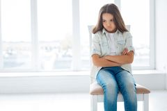 Sad  angry girl offended by her mom. Hurting my feeling. Unhappy irritated dissatisfied  sitting on the chair with crossed arms while looking aside and making Stock Photo