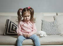 Sad or angry little girl, victim, holding toy dog. Sad or angry little girl, victim, holding toy dog royalty free stock photos