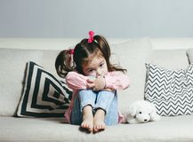 Sad or angry little girl, victim, holding toy dog. royalty free stock photo