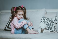Sad or angry little girl, victim, holding toy dog. royalty free stock photography